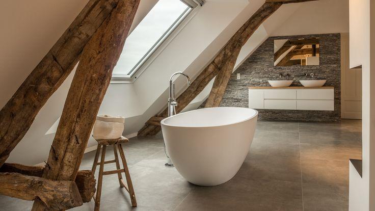 Het vrijstaande Corian bad staat precies tussen de 2 oude spanten. Een groot dakraam geeft veel licht op het bad.