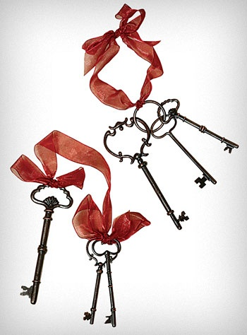 "Sophisticated Skeleton Key Set  Add some vintage style to your decor with these unique skeleton key ornaments. Each of the deep red organza ribbons includes 3 decorative antiqued copper keys. Hang them on a wall, or wrap them around a doorknob to add a unique Victorian inspired touch to your space.  * Set of 2 Ribbons and 6 Keys  * Antiqued Finish   * Keys: 2.5"" - 5"" long each   * Cast Metal  $14.00"