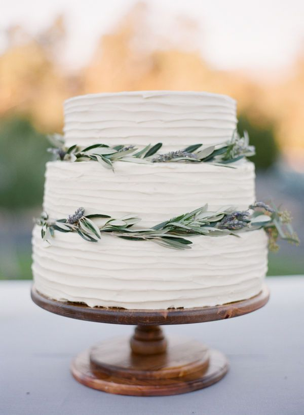 You won't see a piped buttercream wedding cake, nor an elaborately decorated fondant confection at a minimalist wedding. The cake should look be muted, embellished with small amounts of greenery.