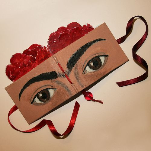 Frida Kahlo Minibook - cover by Paperfection, via Flickr. Frida Kahlo with her trademark unibrow, a stern and somewhat sad look in her eyes and roses in her hair.