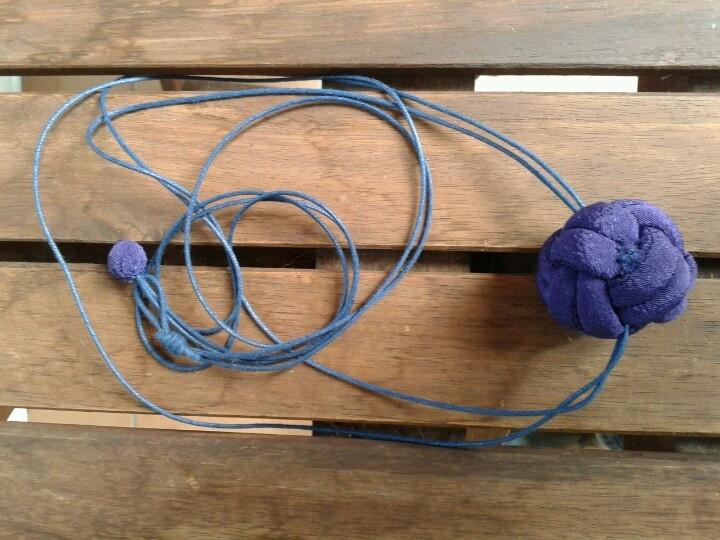 Collaret de roba i cordó. Bola lila feta a base de nusos.