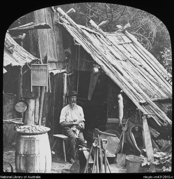 King, Henry, 1855-1923. Man stroking a cat whilst sitting outside a bush humpy, Australia, ca. 1887 [transparency]