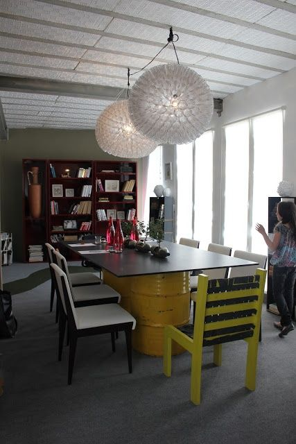 Sala de jantar alternativa. Mesa com base de tambores de lata e tampo de madeira