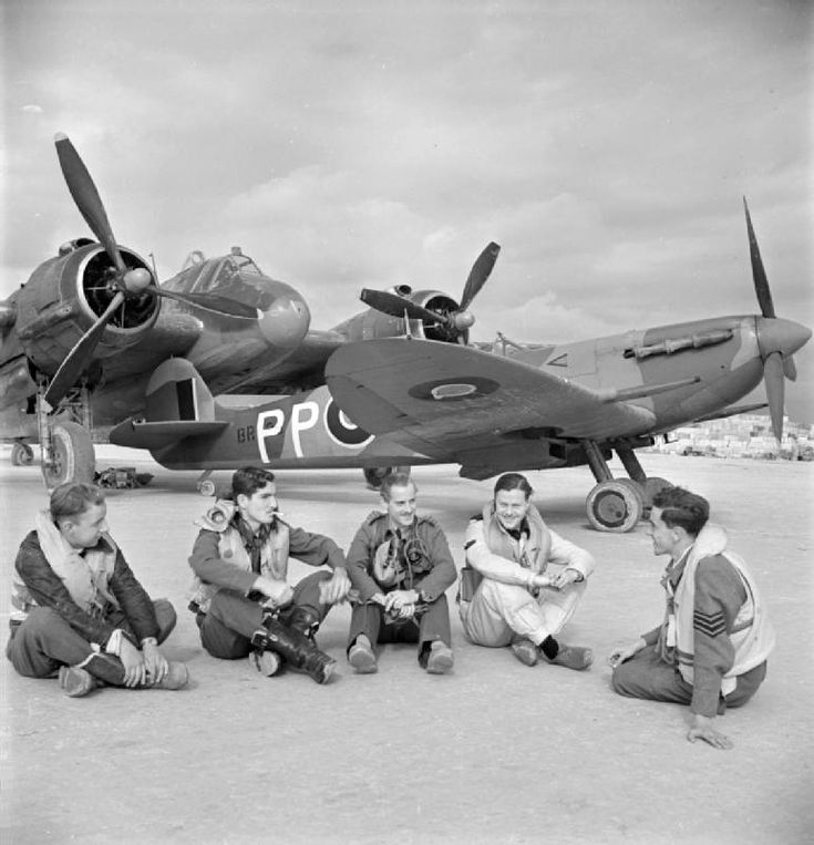 Malta-based pilots sitting in front of two fighter aircraft at Luqa, Malta. Third and fourth from the left: Wing Commander J.K. Buchanan, Commanding Officer of No. 272 Squadron RAF, and Wing Commander M.M. Stephens, leader of the Hal Far Fighter Wing, shortly before the end of his tour of operations. Behind them a Supermarine Spitfire Mark VC, BR498 'PP-H' and a Bristol Beaufighter of No. 272 Squadron RAF.