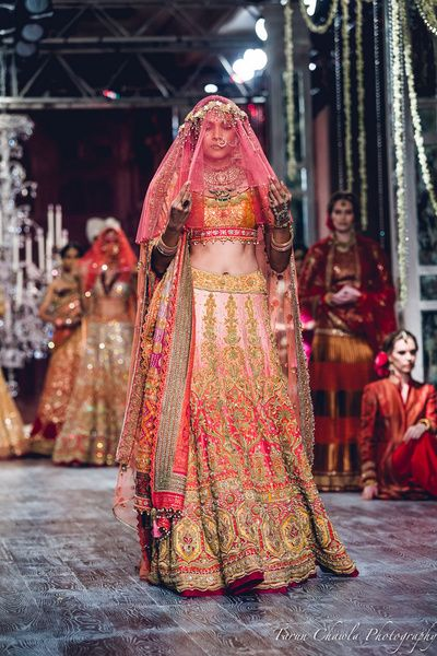 Bridal Lehenga - Heavy Embroidered Tarun Tahiliani Bridal Lehenga | WedMeGood | Pink and Orange Heavy Gold Embroidered Lehenga with Double Dupatta and a Pink Veil Picture Courtesy: Tarun Chawla Photography #wedmegood #indianwedding #indianbride #lehenga