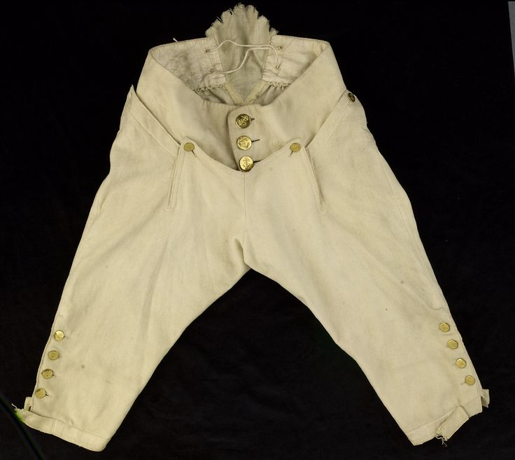 Royal Navel uniform breeches, c.1774, England, brass, horn, linen, silk, wool.  In 1774 the uniform regulations changed and blue breeches that were stipulated in the 1748 regulations were replaced with white breeches. These have a linen gusset in the back of the waist. The eyelets on either side were for linen tapes that would have been used to adjust the fit. The four buttons on each of the knees are of horn, faced with brass that has been die-stamped with the foul anchor motif.