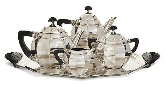 """Maurice DUFRÈNE pour GALLIA (1876-1955) Service à thé et à café en métal argenté et prises en bois, composé d''une théière, d''une cafetière, d''un pot à lait, d''un sucrier et d''un plateau à prises en bakélite. Signé du poinçon """"Orfevrerie Gallia"""" et numéroté. Dimensions diverses."""