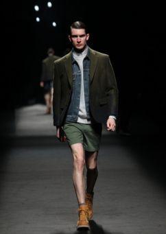 Setelan jas yang formal dibuat kasual dengan memadukannya bersama jaket denim, celana pendek, dan ankle boots.
