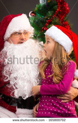 Surprised little girl looking at fake Santa Claus with fake beard. Pulling fake beard down while sitting on Santa Claus lap  - stock photo