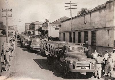 """Nas fotos acima e abaixo, o primeiro GMC, modelo """"grande"""" e com rodas raiadas, é ano 1953 e já está emplacado. Os modelos a seguir são ano 1954. Na foto acima, importante observar as placas na fachada do prédio da agência : """"Caminhões GMC"""", """"GoodYear"""" e """"Pontiac""""."""