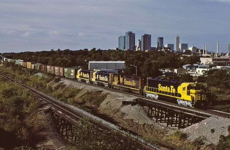 https://flic.kr/p/Dczxsy | 4th of July Treat | Fresh out the paint booth at Cleburne, Santa Fe SD45-2 5637 leads a freight towards Gainesville with downtown Ft Worth in the background. He's in full dyno approaching the Trinity River bridge about 1/4 mile ahead of him. As soon as he gets across the bridge and the power clears the diamond at Tower 60, he'll throttle up for the pull to Saginaw on the north side of Ft Worth.