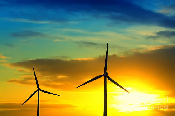 Wind And Sun Energy Photograph. Two windmills producing green energy during sunset showing a cloudscape with vibrant sky colors.