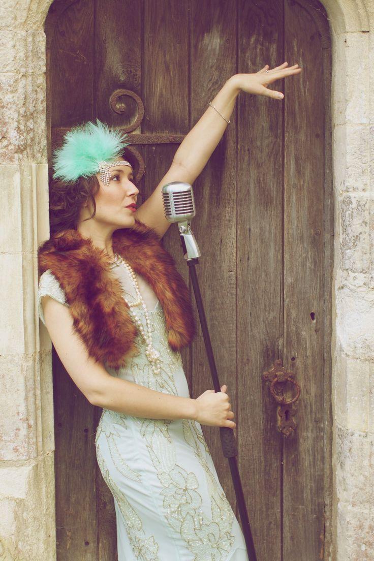Vintage 1920s style photoshoot. Great Gatsby era, Jazz singer portraits. Vintage microphone, blue dress, pearls, blue feather & diamanté headdress, fake fox fur, red lipstick. Vintage glamour and style inspiration. Www.fionamillsart.com