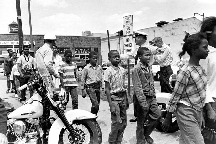Policemen are lead a group of black school children into jail, following their arrest for protesting against racial discrimination near the city hall of Birmingham, Ala., on May 4, 1963