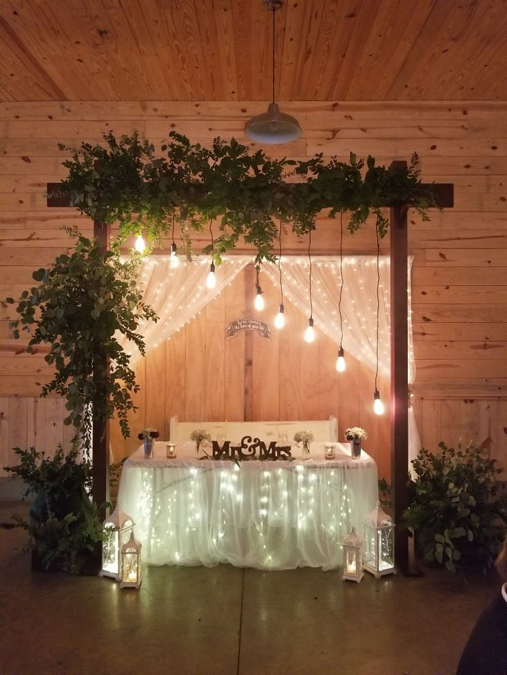 Collapsible ceremony and reception arch greenery and Edison bulbs