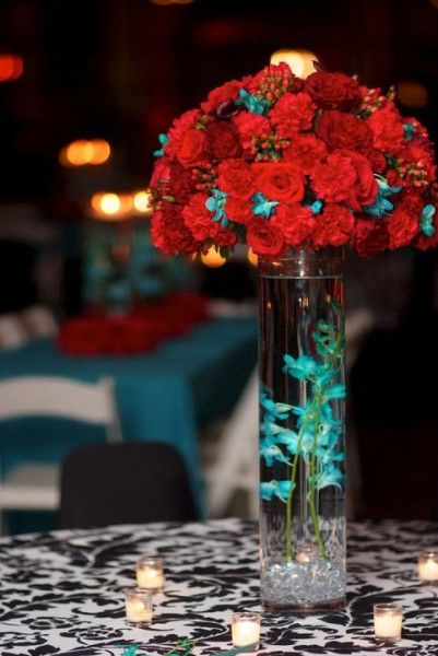 Love the idea of floating flowers in the tall vase with burst of flowers at the top..would pick a different color instead of red roses