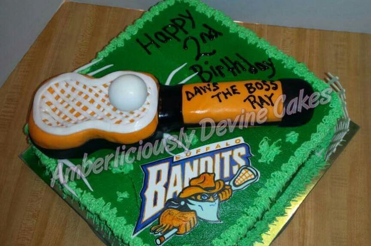 A Buffalo Bandits lacrosse themed cake. A lacrosse stick, ball & net. Also a bandits logo on a grass playing field. Www.facebook.com/AmberliciouslyDevineCakes