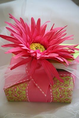 """Hot pink gerbera daisy with a matching """"stitched"""" ribbon tops this lovely little gift."""