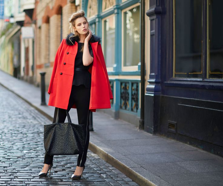 Red military-inspired coat with faux-fur collar, worn over black peplum top and fitted trousers with contrast stripe, all Savida by Dunnes Stores
