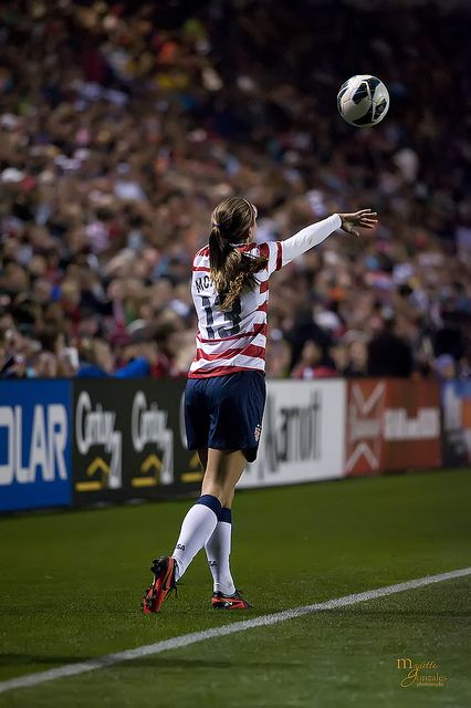Alex Morgan doing a throw in.