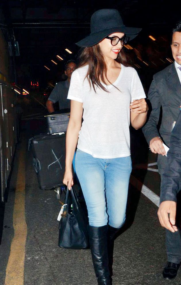 Deepika Padukone arrives at 4 am looking radiant in a pair of jeans and a white T-shirt and poses for the shutterbugs.