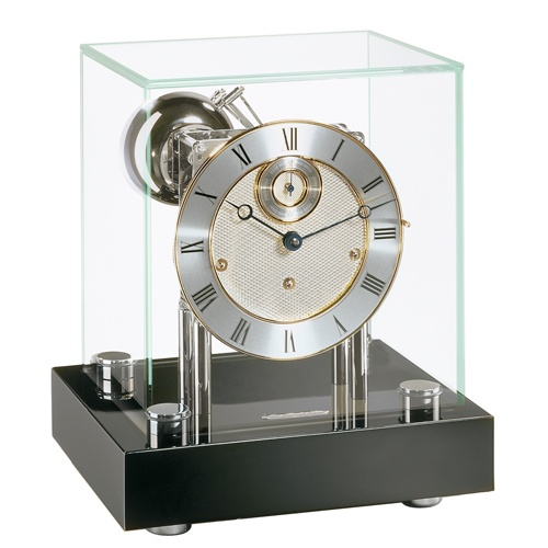 The Chigwell Mantel Clock by Hermle was inspired by the minimalist elegance of the cube. This polished, nickel-plated Westminster 352 movement is supported by heavy pillars mounted on the black piano finish wood base. This 8-day spring wound, Westminster movement chimes on four bells, features a polished nickel–plated finish and a 11 jewel deadbeat escapement with a separate second feature. http://www.theclocksshop.com