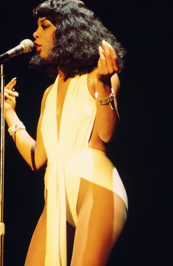 Donna Summer The oh-so seductive Donna Summer exuded every bit of the sexiness she sung about in her stage ensembles. The Queen of Disco bared-all confidently in shiny leotard wraps, this 1977 style in particular was a look we loved.