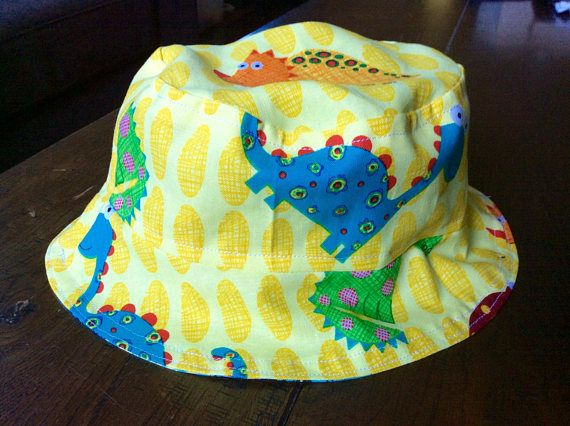 Handmade from high quality soft cotton fabrics, these reversible sun hats for small children feature a cute yellow dinosaur print fabric on one side and on the other, a blue fabric with Kombi van print. They are available in four sizes: Baby (head circumference up to 45cm) Infant (45 - 48cm) Toddler (48 - 51cm) Preschooler (51 - 53cm) Please specify the size required in the comment box upon purchase.