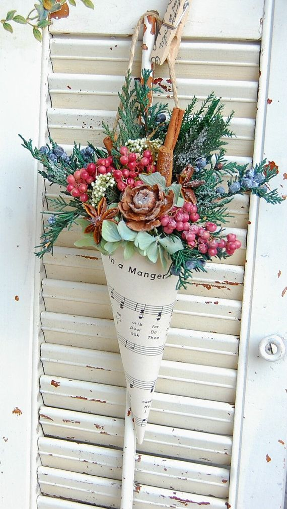 Vintage Christmas Sheet Music paper was used to create a sweet holder for preserved greens, berries, cinnamon sticks , star anise and a cedar rose