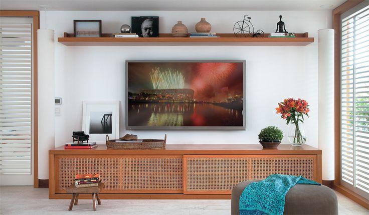 """Como o ambiente é amplo (60 m²) e poderia passar a sensação de vazio, a ideia foi buscar o aconchego por meio de materiais como tijolos e a palhinha das portas do aparador (execução da Serla). """"Ela não barra a saída do som dos equipamentos"""", destaca a arquiteta Maria Eduarda Gomide. A fiação da TV (Samsung de 64"""") fica embutida na parede."""