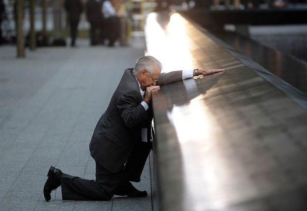 Robert Peraza, who lost his son Robert David Peraza in 9/11, pauses at his son's name at the North Pool of the 9/11 Memorial.