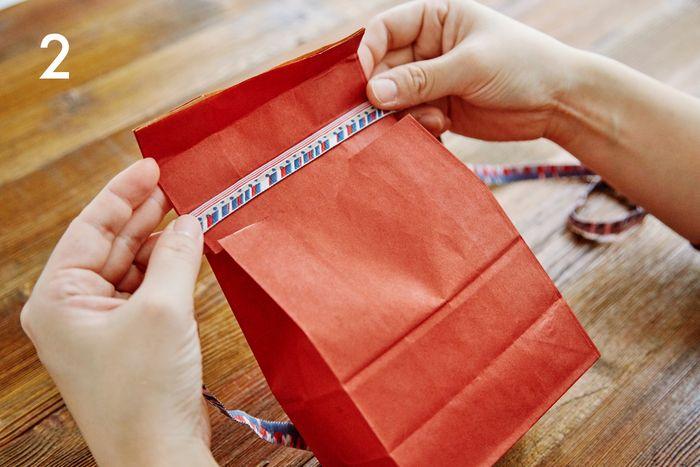 折った部分を一度広げ、リボンを巻き込むように、再び折り直します