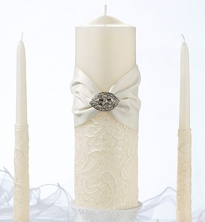 "- This elegant cream candle set has the antique look and lace design.  This candle is wrapped in cream satin and beautiful gem.  Pillar and tapers have an elegant design of lace.  Set comes with one cream coloured wax 8.5"" pillar and matching two 10"" tapers."