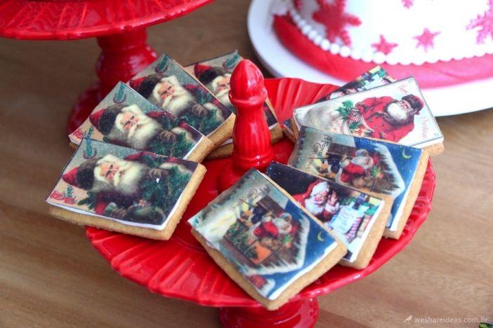 biscoitos de natal em forma de cartão de natal sobre pratos de bolo vermelhos. Super fofo para decorar a mesa.
