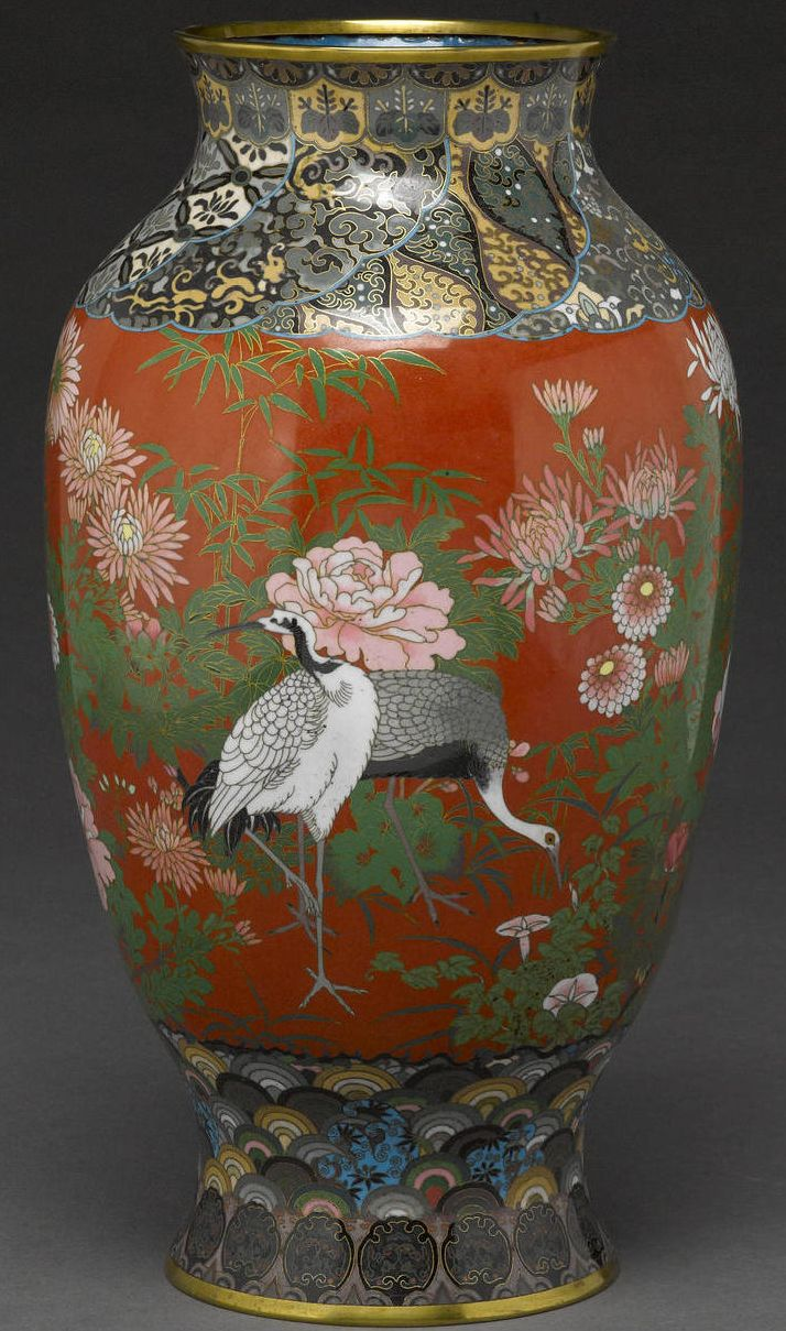 A cloisonné enamel vase Meiji period The ovoid body decorated bright enamels with cranes in a landscape with flowering bushes and bamboo defined in gilt and silver cloisons on a brick red ground, brocade-patterned bands at the shoulder and waisted neck, the flaring base with a seigaiha band above a border of dissolving zoomorphic cartouches, gilt metal rims.