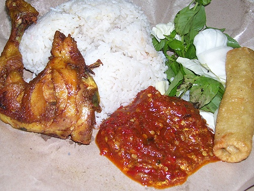 Nasi Uduk + Pecel Ayam Don't know why they call it Pecel Ayam when there is no nut sauce, but that red hot chilly is really good. Nasi uduk is rice cooked with coconut puree. Add a little gorengan, and its a perfect lunch.