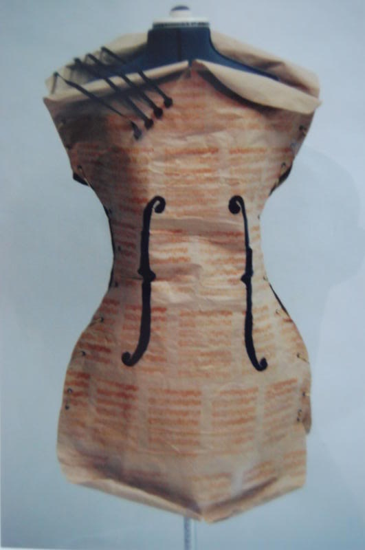 Violin dress  This dress is made from brown paper, black & gold ribbon, rivets, pom-poms and a manuscript stencil. With all the simple materialsand inspiration from Man Ray,