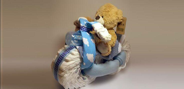 Plienkova torta - Maco - motorkár. Je zložený iba z vecí, ktoré dieťa potrebuje: 36 plienok (Happy, veľkosť 2), dve deky, chlapčenské body, jeden pár ponožiek, fľaša pre kojenca a plyšový maco.
