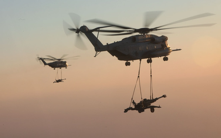 Two U.S. Marine Corps CH-53E Super Stallions with Marine Heavy Helicopter Squadron (HMH) 361, Marine Aircraft Group 16, 3rd Marine Aircraft Wing (Forward), lift M777 howitzers over Helmand province, Afghanistan, on December 29, 2012. (USMC/Sgt. Keonaona C. Paulo)