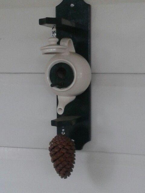 Theepot vogelhuisje. Een plaatje hout in theepot-opening met een vogelgaatje erin en een zitstokje ervoor.Theepot-dekseltje aan stukje ketting hangt aan afdakje met haakje en mooie dennenappel of wat anders hangt aan haakje aan onderkant. Leuk!