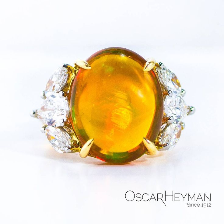 An 11ct Fire opal ring with gold prongs, set with marquise and pear shape diamonds in platinum by Oscar Heyman