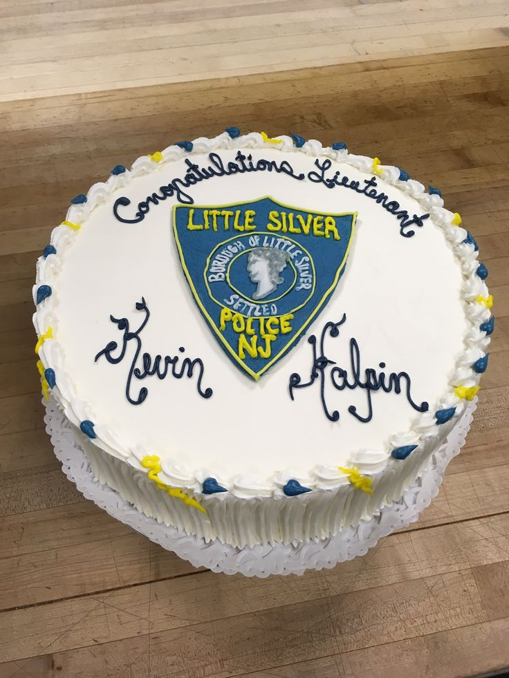 A congratulatory cake for an officer's promotion, a hand drawn buttercream shield representing the town of Little Silver.