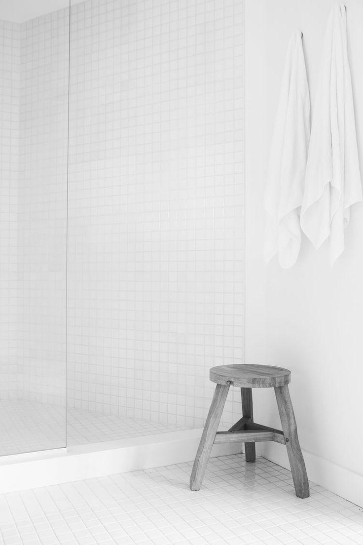 白いタイル張りのバスルームのコーナーに炭のグレーのようなスツール