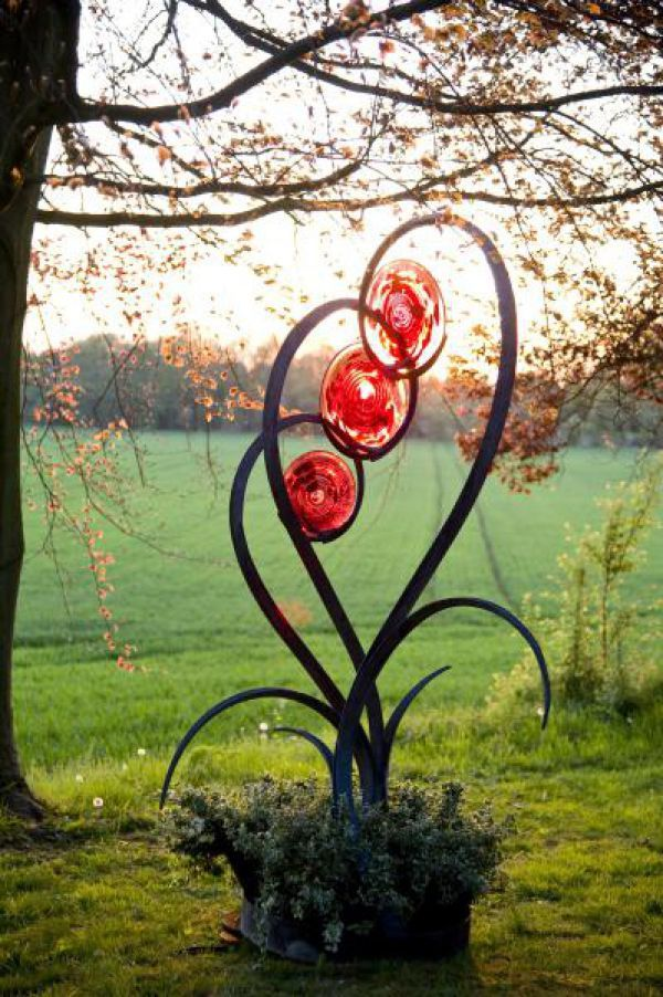 Forged steel and blown glass Abstract Garden sculpture by artist Jenny Pickford titled: 'Unfurl (Outsize Steel and Glass Flower Plant Sculptures)'