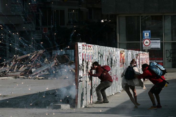 Protesters take cover behind a barricade as fireworks go off nearby in Taksim Square, on June 11, 2013