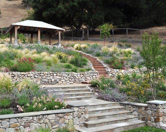 jardin en pente avec murets de pierre naturelle et herbe aux écouvillons