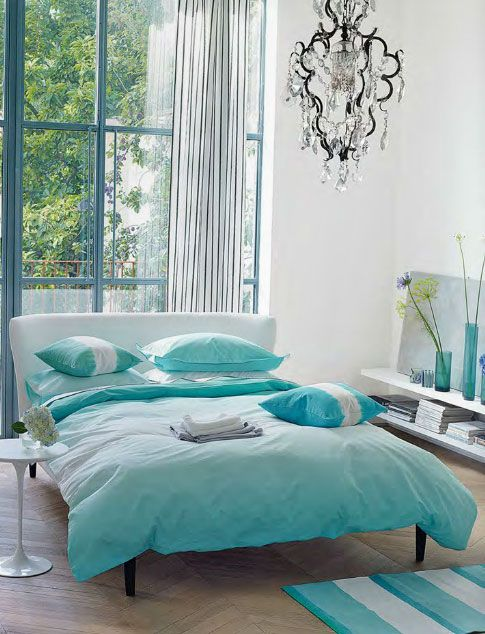 Amazing, fresh bedroom with big windows leading out to a balcony, pretty crystal chandelier and dip-dyed aqua bedding and pillows. BUY the bedding in this picture here: Saraille Aqua bed Linen