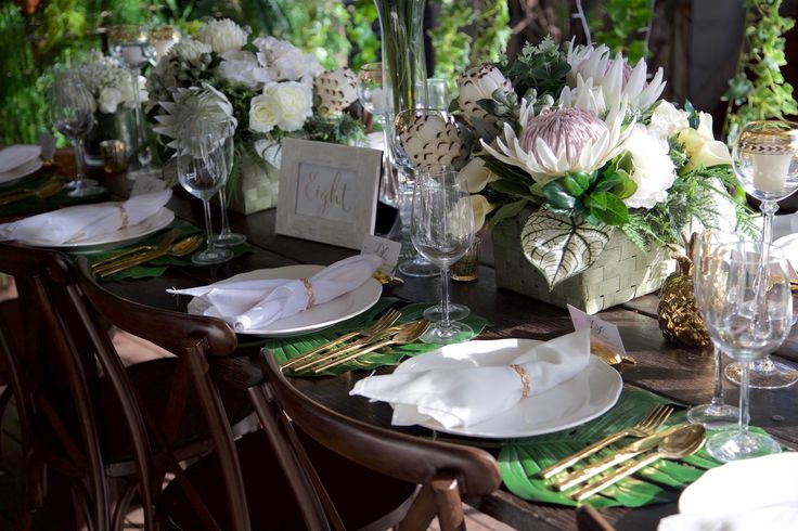 White tropical floral centrepieces with gold accents