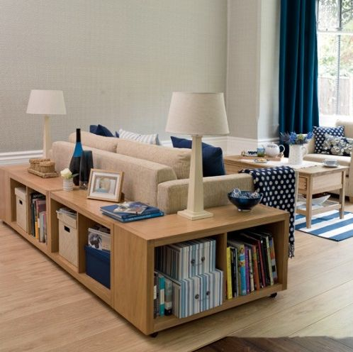 This clever room has a bookcase wrapping around the sofa, which serves  double duty as
