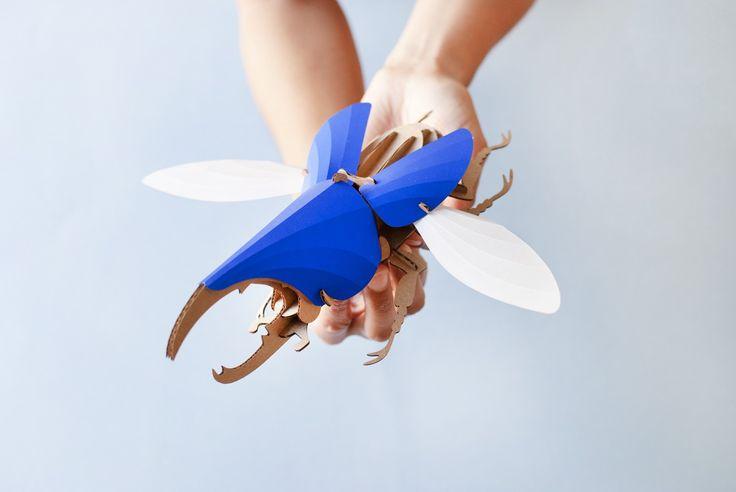 """Assembli est une marque hollandaise d'objets de décoration pour des intérieurs originaux et contemporains. Le designer de la marque, Joop Bource, vient de concevoir ce trio coloré mixant sculpture en papier, insecte et DIY.  En effet, ces trois kits de montage proposent de créer vous-même de magnifiques scarabées, chacun d'une espèce différente: le dynaste hercule, le lucane cerf-volant et le scarabée-atlas. Vous recevez le kit avec tous les éléments """"à plat"""", il ne vous reste qu'à suivre..."""